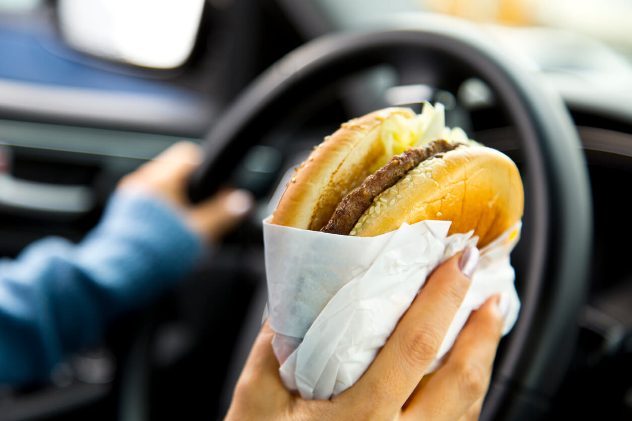 Woman holding a burger while driving