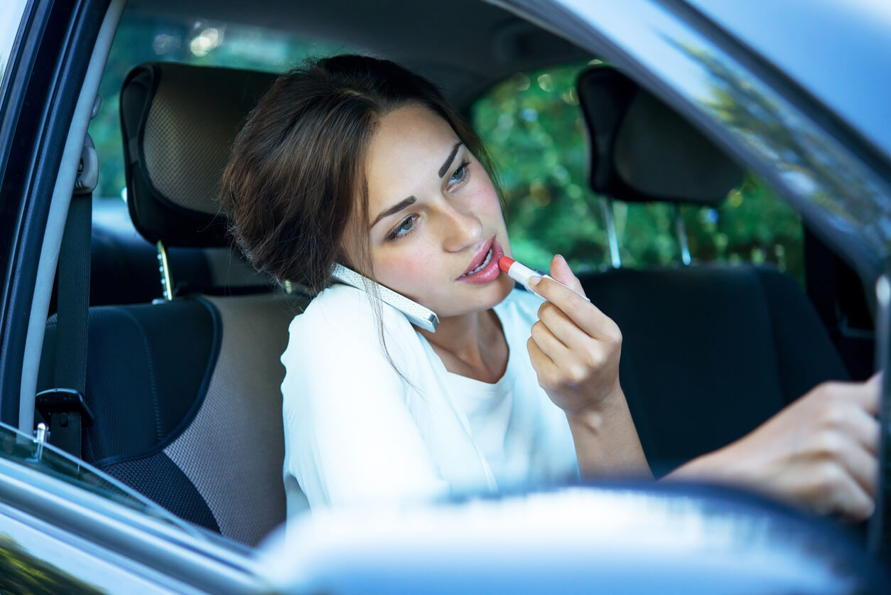 Woman applying lipstick and on phone while driving