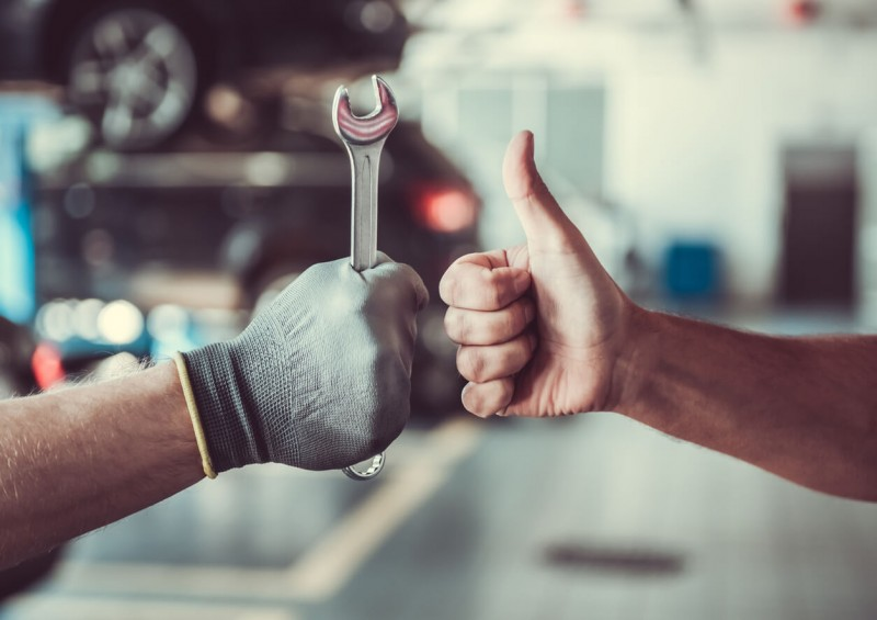 A mechanic holding a spanner and thumbs up
