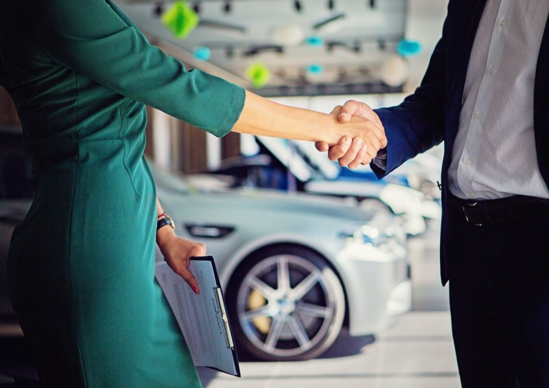 Car dealer and customer shaking hands over a car deal