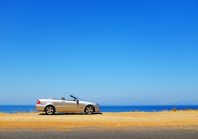 Convertible car parked near the coast with blue sky