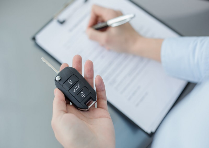 Customer holding car key and signing contract