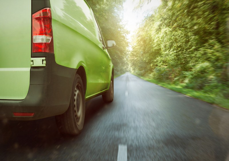 Green van driving with forest on both sides