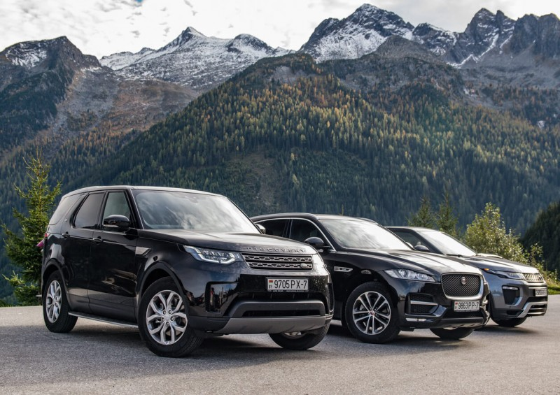 Land Rover and Jaguar SUVs in front of mountains