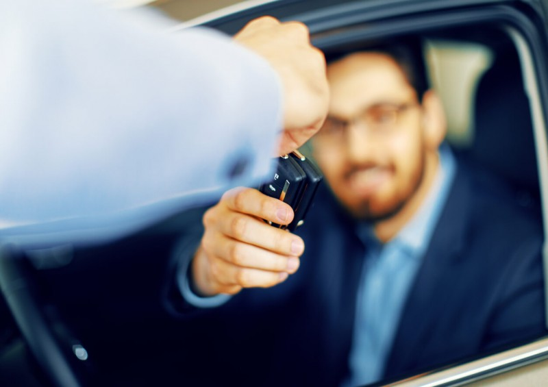 Man handing new car keys over to driver