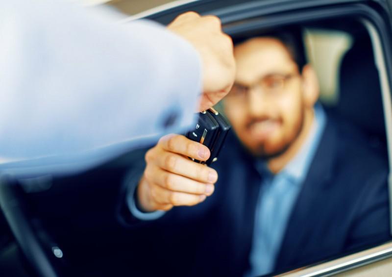 Man handing new car keys over to driver