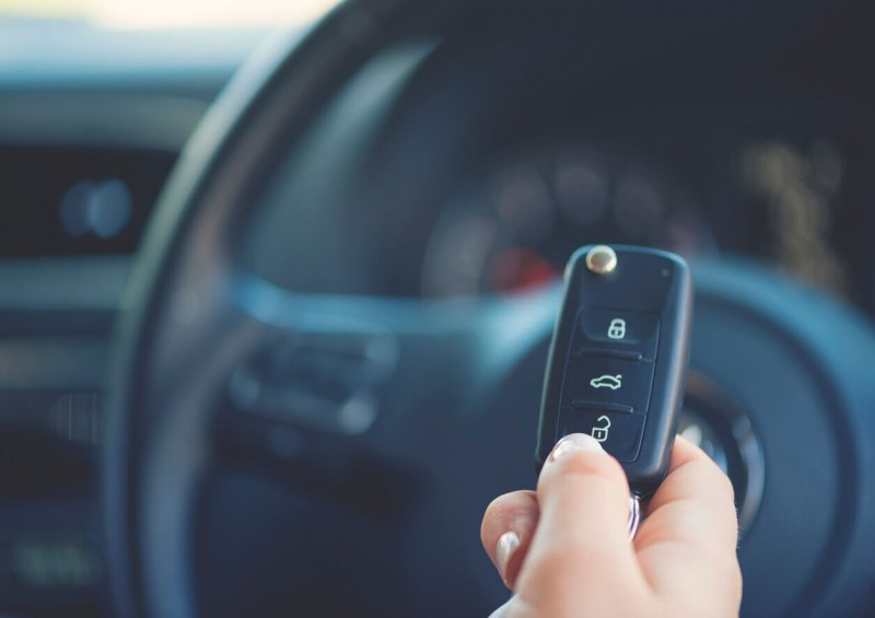 Person holding car keys in front of steering wheel