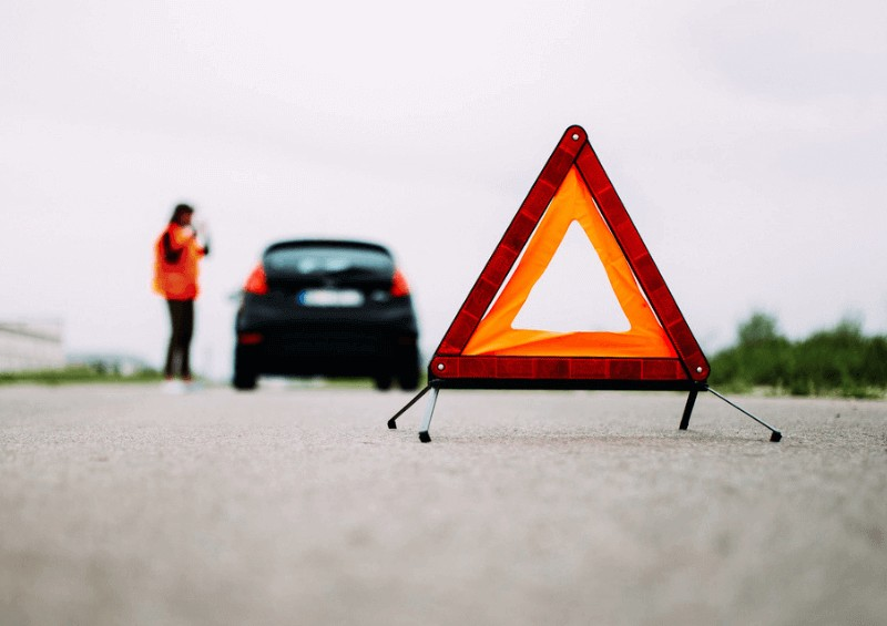 Person waiting by their broken down car and safety triangle