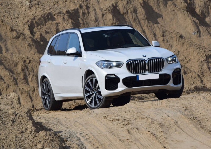 White BMW X5 parked on dunes